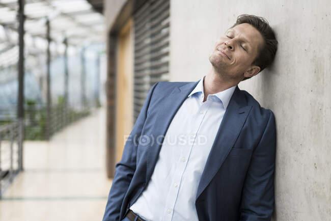 Бізнесмен відпочиває з закритими очима, спираючись на стіну. — стокове фото
