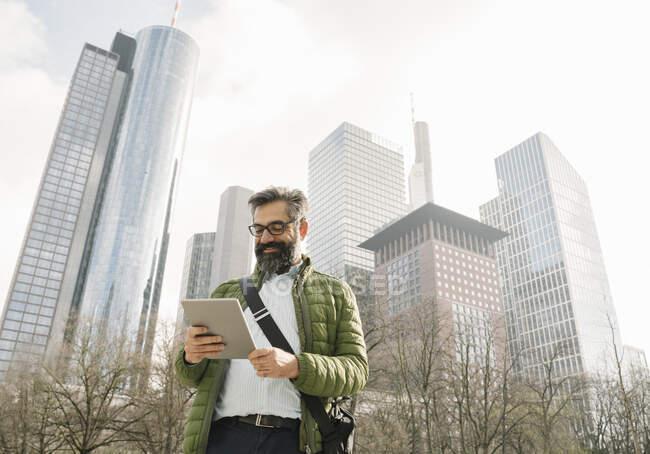 Людина, яка користується планшетом перед хмарочосами у Франкфурті (Німеччина). — стокове фото