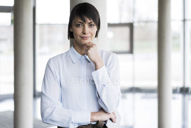 Serene businesswoman standing in bright office building — Stock Photo