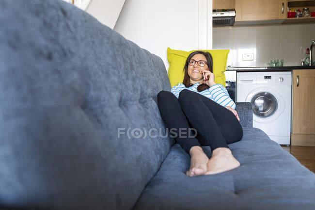 Mujer hablando por teléfono y sentada en el sofá en casa - foto de stock