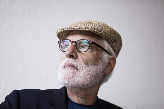 Портрет бородатого старшого чоловіка з білим волоссям в шапці дивлячись на відстань — стокове фото