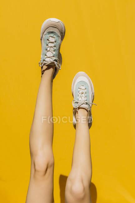 Pernas de mulher em sapatos esportivos sobre a parede amarela durante o dia ensolarado — Fotografia de Stock