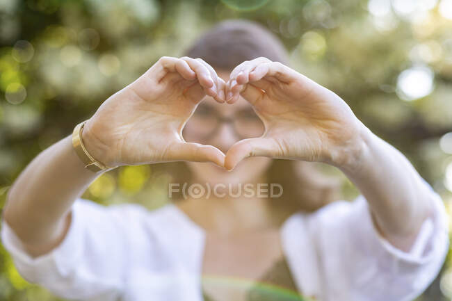 Young woman forming a heart with her hands — Stock Photo