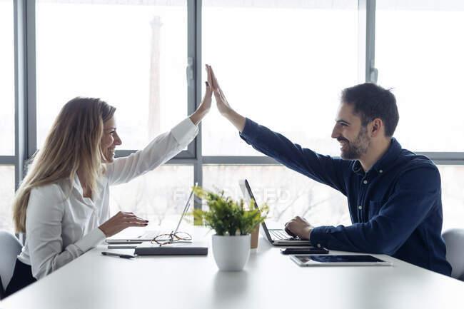 Бізнесмен і жінка сидять за столом, використовуючи ноутбуки, високі п