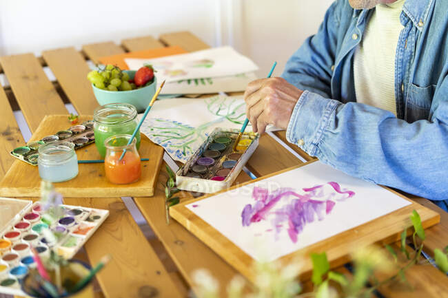Homem sênior mergulhando pincel em tintas aquarela na mesa em casa — Fotografia de Stock