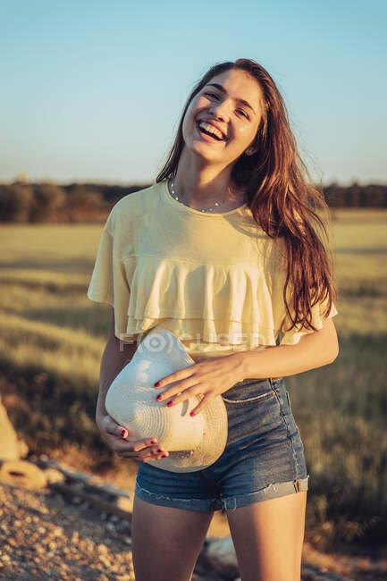 Веселая молодая женщина, держащая шляпу солнца, стоя на поле против ясного неба во время заката — стоковое фото