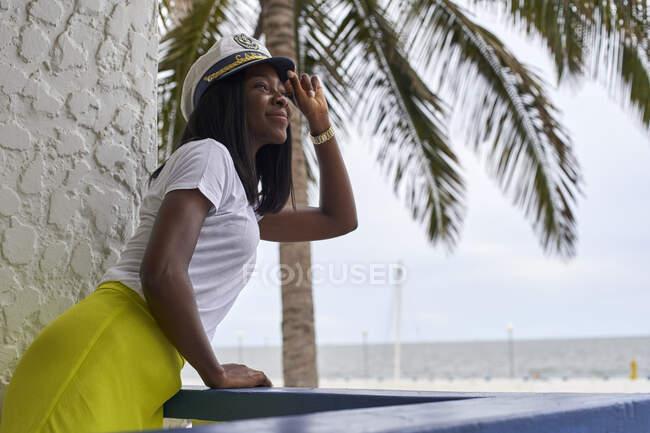 Счастливая молодая женщина в капитанской шляпе стоит на террасе и смотрит — стоковое фото