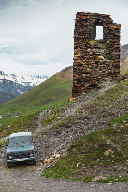 Джорджія, Сванеті, Ушулі, Старий автомобіль, припаркований перед старою середньовічною цегляною вежею. — стокове фото