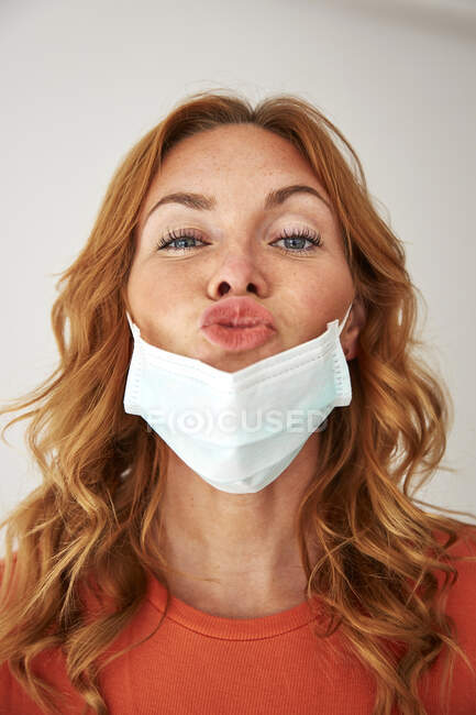 Retrato de mujer pelirroja con labios besos sobre una máscara protectora - foto de stock