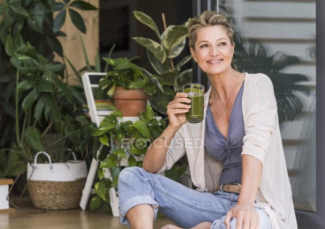 Retrato de mujer madura relajada sentada en la puerta de la terraza abierta con vaso de batido verde - foto de stock