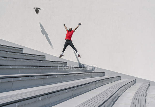 Esportista usando máscara facial pulando em escadas com pássaro voador — Fotografia de Stock