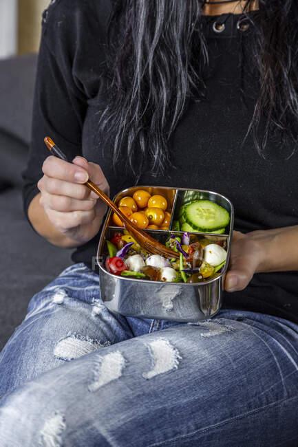 Parte média da mulher sentada e comendo da lancheira — Fotografia de Stock