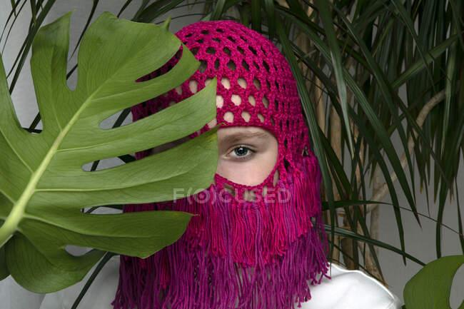 Retrato de adolescente con tocado rosa de ganchillo escondido detrás de la hoja de Monstera - foto de stock