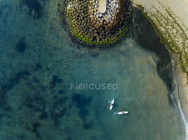 Індонезія, Балі, Санур, Повітряне видовище двох серферів перед скелястим узбережжям. — стокове фото
