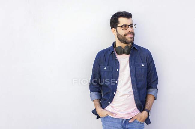 Портрет улыбающегося человека с беспроводными наушниками, смотрящего на расстояние — стоковое фото