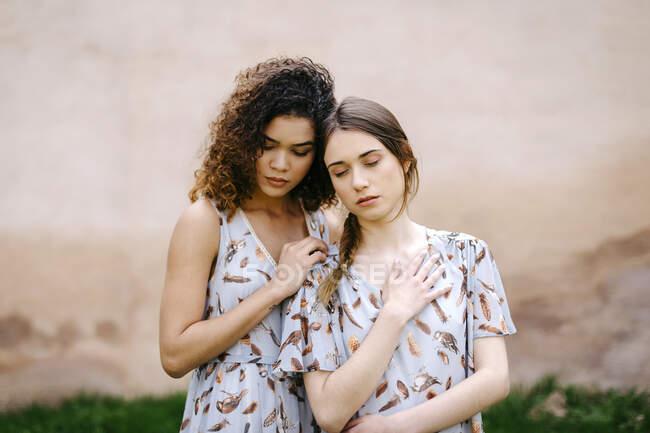 Aimant sœurs avec les yeux fermés embrassant tout en se tenant contre le vieux mur — Photo de stock