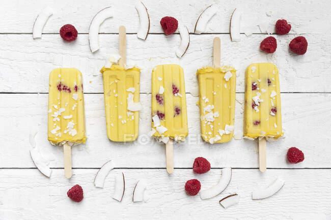 Popsicles maison à la mangue et à la framboise avec copeaux de noix de coco — Photo de stock