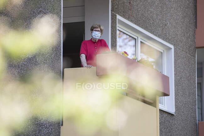 Mujer mayor con máscara en el balcón, casa de retiro - foto de stock