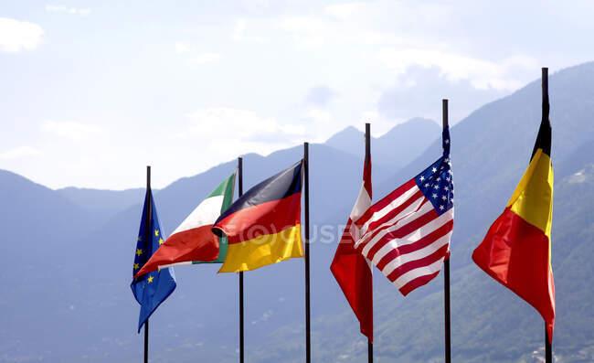 Germania, Bandiere nazionali sventolanti contro la valle della montagna — Foto stock