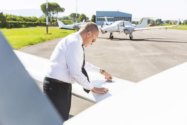 Pilot doing pre flight inspection on his sports plane — Photo de stock