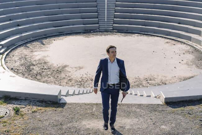 Hombre de negocios maduro en un anfiteatro en un sitio de punta de mina en desuso - foto de stock