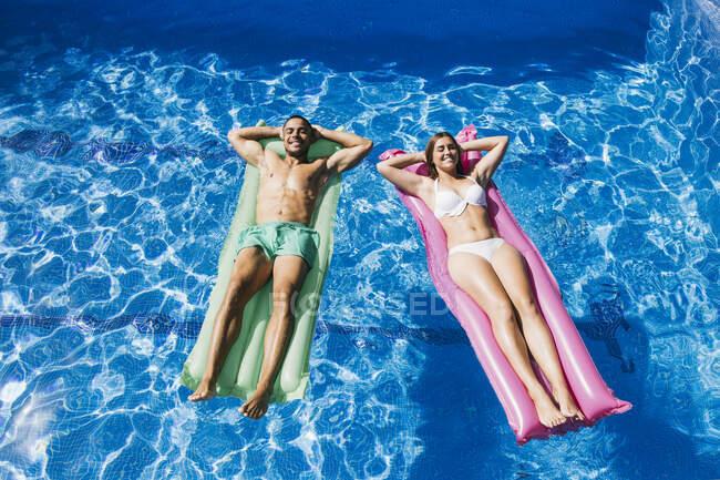 Sorridente giovane coppia con le mani dietro la testa rilassante su airbeds in piscina — Foto stock