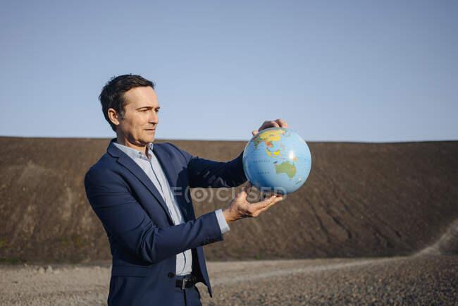 Зрілий бізнесмен тримає глобус на занедбаному кінці. — стокове фото