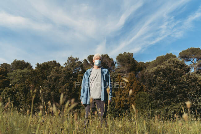 Homem sênior com máscara protetora em pé no prado — Fotografia de Stock