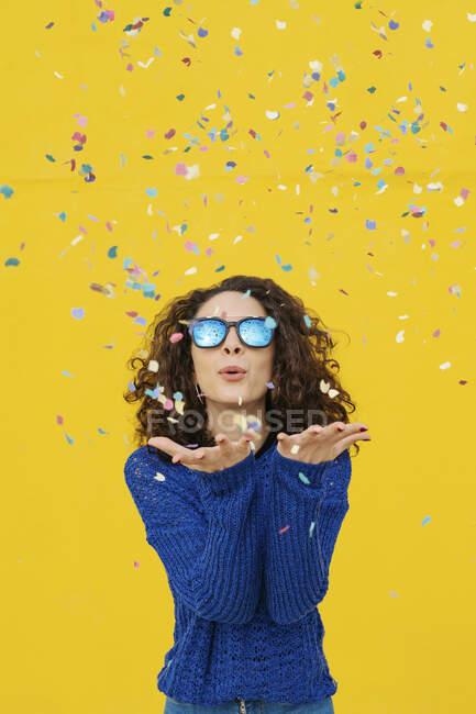 Портрет молодої жінки з дзеркальними сонцезахисними окулярами, що дують конфетті в повітрі перед жовтим фоном. — стокове фото