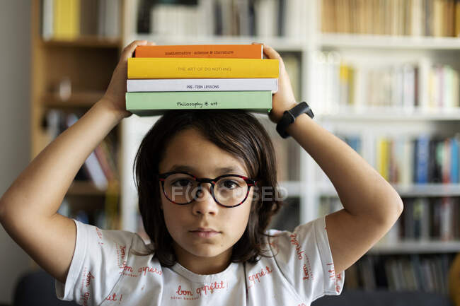 Portrait of serious boy with stack of books on his head — Stock Photo