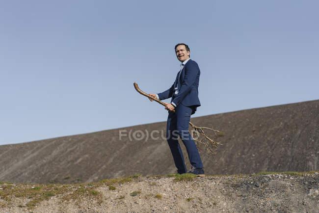 Maduro hombre de negocios montando un árbol desnudo en una punta de mina en desuso - foto de stock