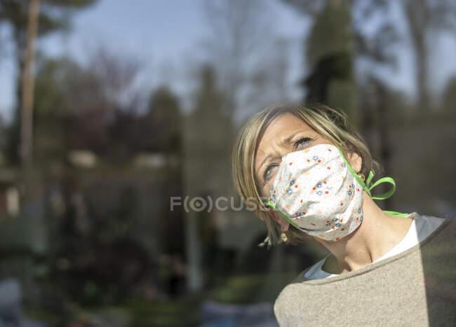 Mulher com máscara facial olhando através de vidro da janela no dia ensolarado durante a quarentena — Fotografia de Stock