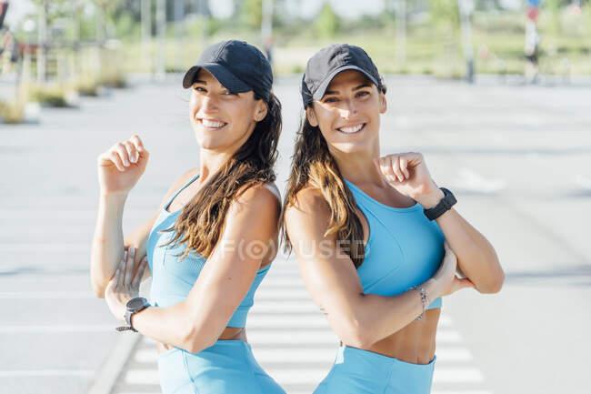 Portrait de jeunes sœurs jumelles souriantes debout sur la route pendant la journée ensoleillée — Photo de stock