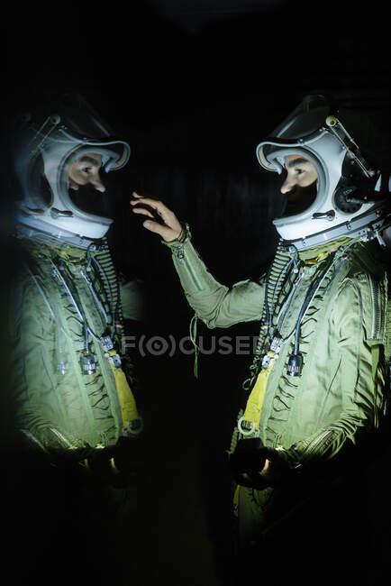 Joven astronauta tocando su reflejo en la oscuridad - foto de stock