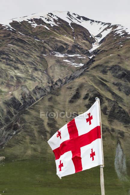 Грузія, Сванеті, Ушулі, вид на грузинський національний прапор, що пурхає на гору. — стокове фото