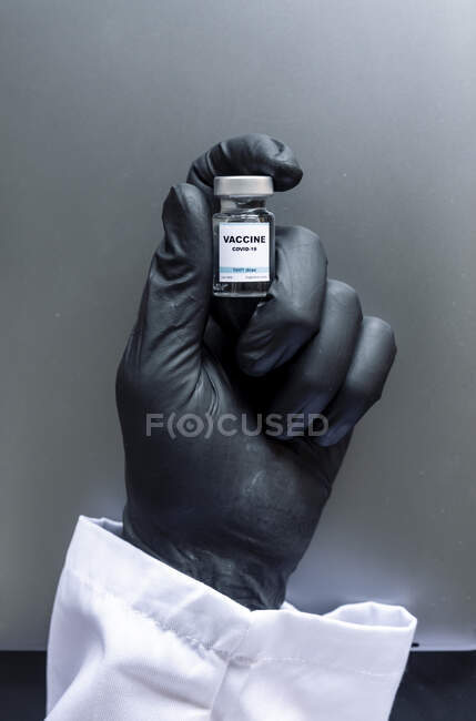 Cropped image of scientist's hand holding COVID-19 vaccine sample at laboratory — Stock Photo