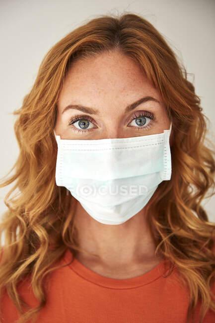 Retrato de mulher ruiva usando uma máscara protetora em casa — Fotografia de Stock