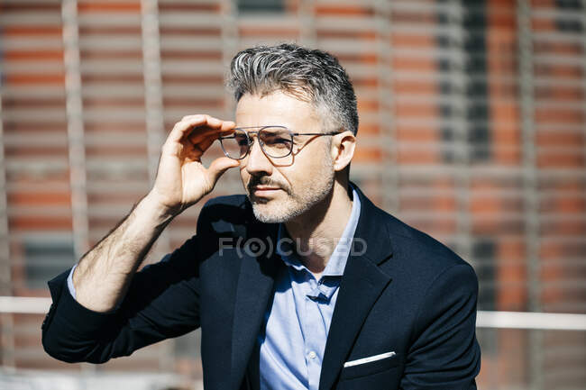 Portrait of a gray-haired businessman in the city putting on glasses — Stock Photo