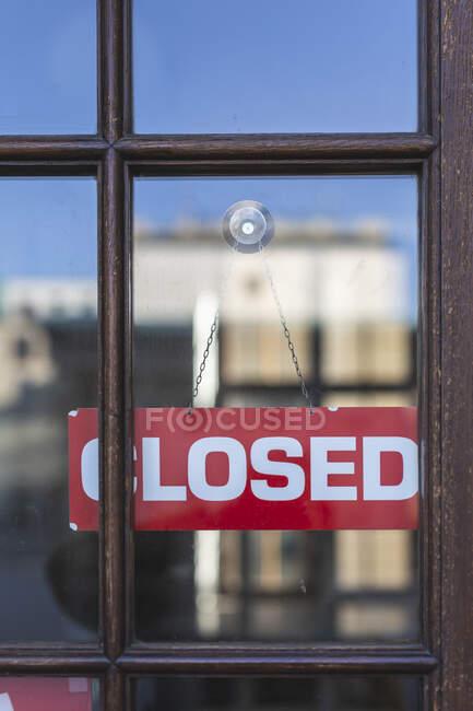 Alemanha, sinal fechado pendurado atrás da janela da loja — Fotografia de Stock