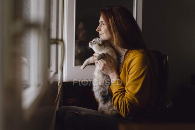 Lächelnde rothaarige Frau sitzt mit ihrer Katze am offenen Fenster zu Hause — Stockfoto