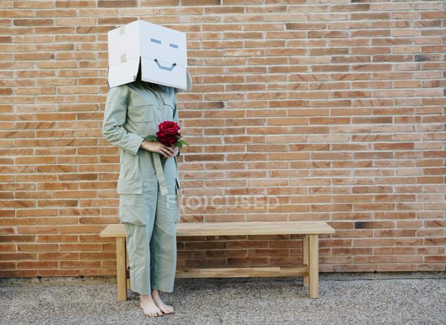 Mujer sosteniendo rosa roja, usando caja de cartón con la cara feliz, de pie junto al banco frente a la pared de ladrillo - foto de stock