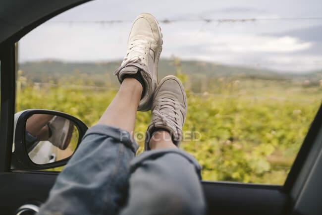 Женские ноги высовываются из окна машины — стоковое фото