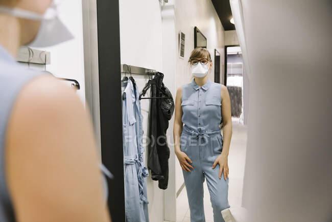 Жінка з маскою обличчя намагається одягнутися в магазин моди. — стокове фото