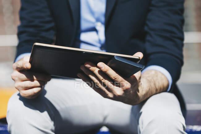 Бізнесмен тримає на вулиці планшет і мобільний телефон. — стокове фото