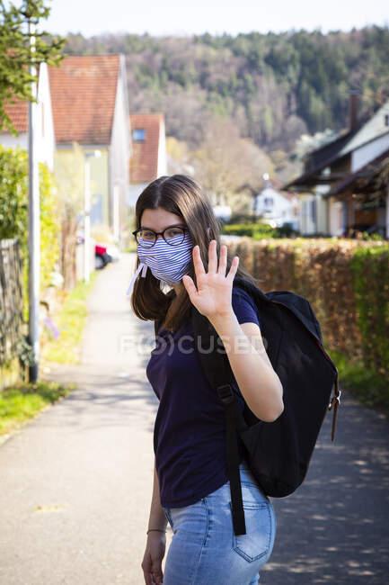 Ragazza adolescente sulla strada per la scuola, indossando maschera — Foto stock