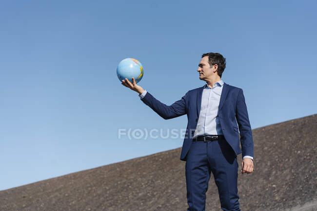 Mature businessman holding a globe on a disused mine tip — Stock Photo