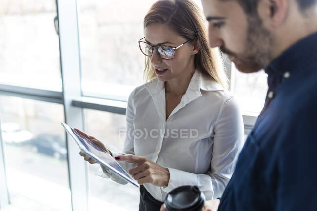 Homme d'affaires et femme travaillant ensemble dans le bureau, en utilisant une tablette numérique — Photo de stock