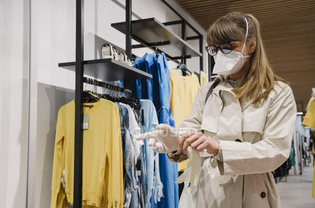 Жінка з масками обличчя одягає одноразові рукавички в магазині моди. — стокове фото