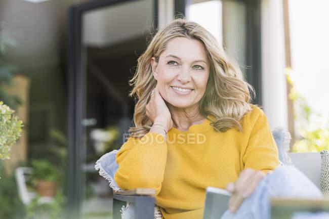 Retrato de mujer madura sonriente sentada en terraza con tablet digital mirando a distancia - foto de stock