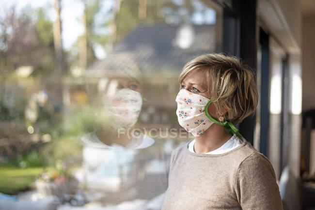 Доросла жінка у квітковій масці, дивлячись через вікно вдома під час ізоляції COVID-19. — стокове фото